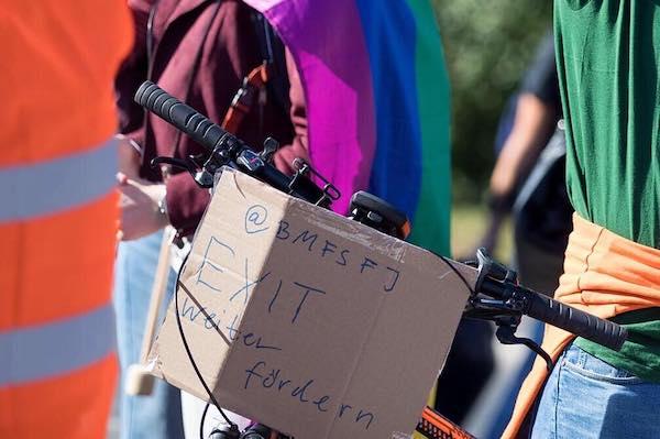 Bild eines Fahrrads mit einem Pappschild, auf dem das Familienministerium aufgefordert wird EXIT weiter zu fördern.