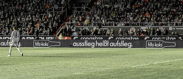 Spielfeldbegrenzung mit einem Banner der Firma Fritz-Kola. Auf dem Banner steht: Ausstieg heißt Aufstieg