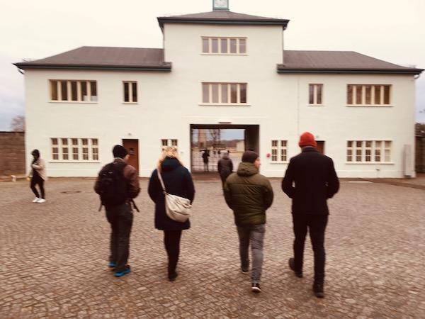 Mitarbeiter von EXIT laufen auf das Tor der Gedenkstätte Sachsenhausen zu